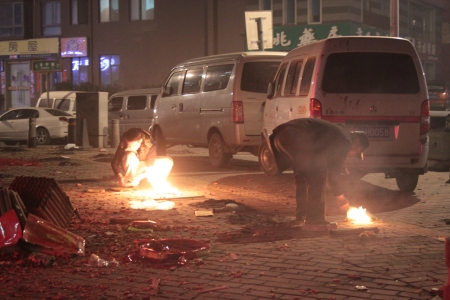 Chinese men lighting fires in the street.