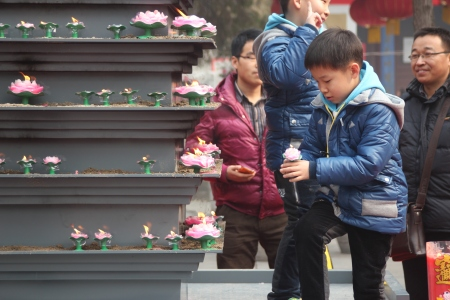 A little boy lighting a candle at the temple.