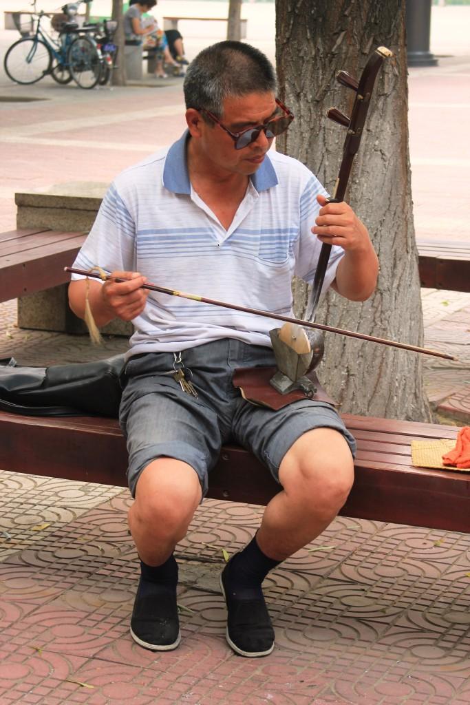 A man playing his home-made erhu in the park.